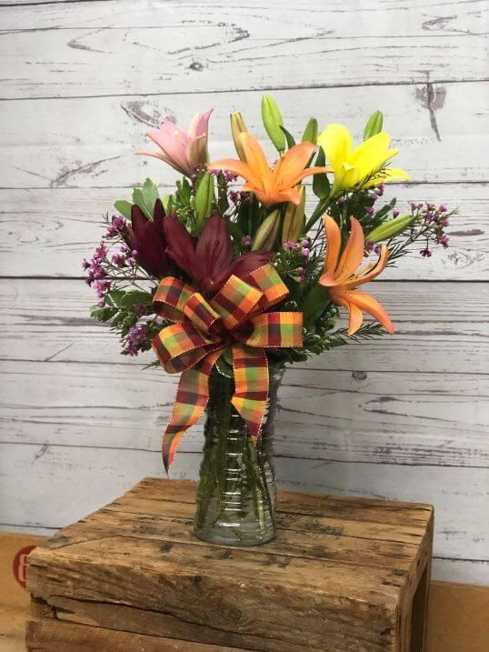 ONLINE EXCLUSIVE SALE! NOW $5 OFF WHEN YOU ORDER ONLINE! Evolution In Lilies Vased Arrangement